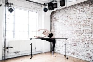 Dancer stretching at ballet barre