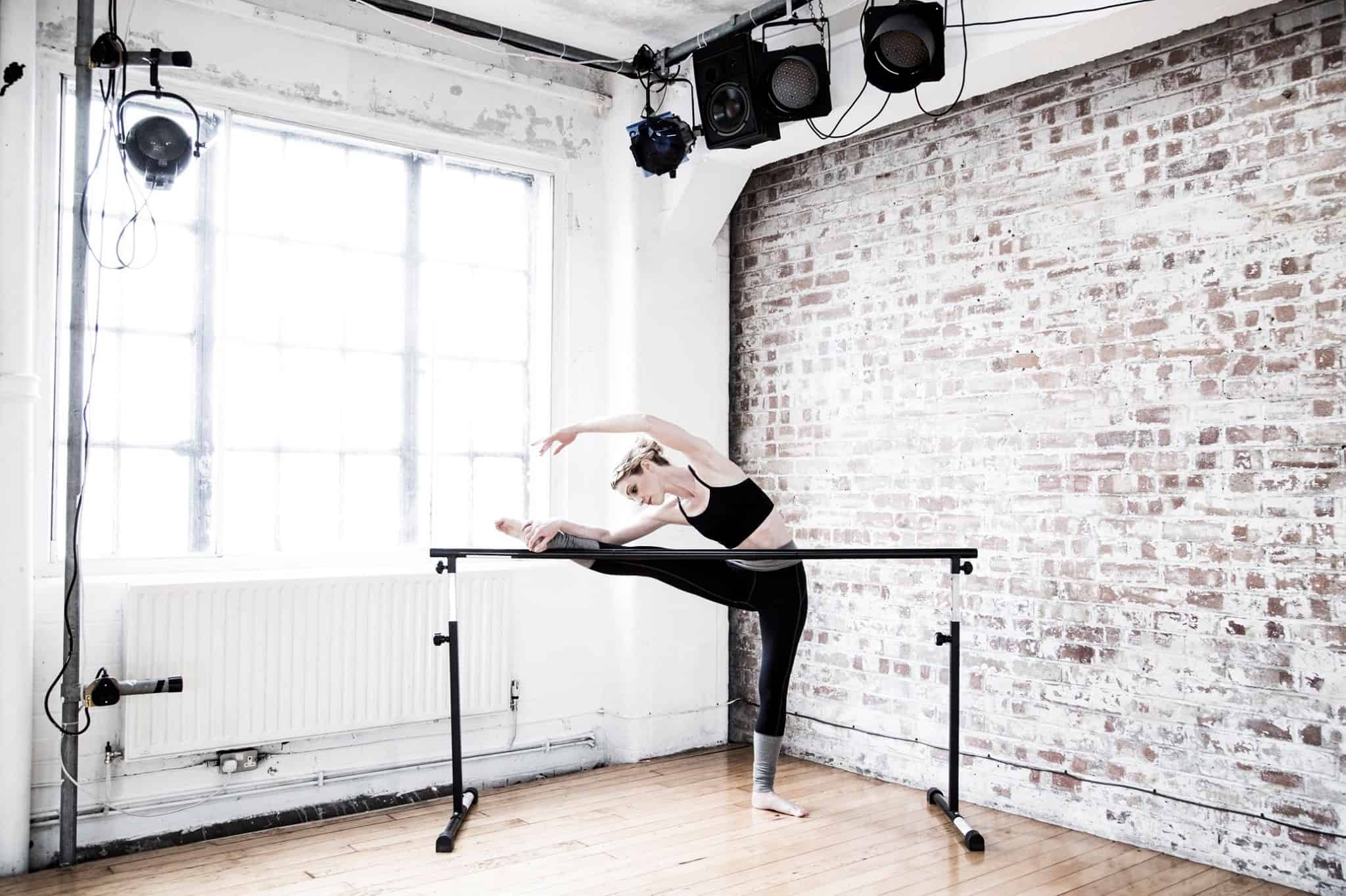 Dancer stretching at ballet barre
