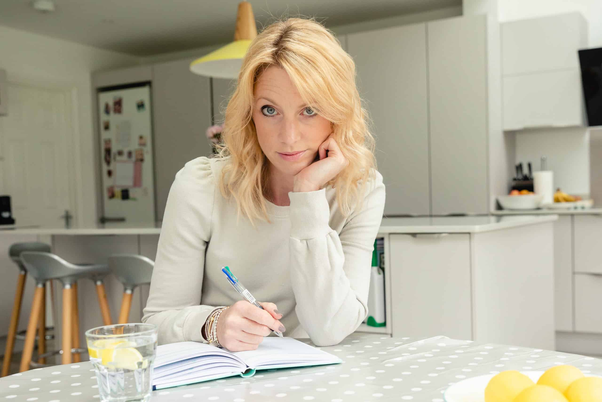 Sarah sitting at kitchen table writing in notebook with lemon water